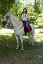 Woman with black hair on a white horse Stock Image
