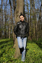 Woman with black leather jacket and jeans in spring forest a young caucasian a the during early Stock Images