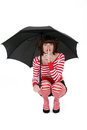 Woman with black umbrella squatting Stock Photos