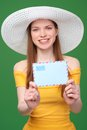 Woman with blank envelope smiling bright in summer dress and white hat giving stretching banner shallow depth of field focus at Royalty Free Stock Photography