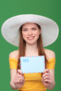 Woman with blank envelope smiling bright in summer dress and white hat giving stretching banner shallow depth of field focus at Royalty Free Stock Images