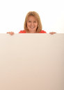 Woman with blank sign portrait of a happy middle aged looking over the top of a board a white studio background Stock Image