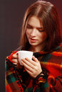 Woman in a blanket cup young caught cold wrapped and something hot drink from Royalty Free Stock Photos