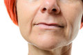 Woman with blemish on chin extreme close up of older red hair a her face against a white background Royalty Free Stock Photo
