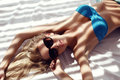 Woman with blond wet hair in elegant bikini and sunglasses Royalty Free Stock Photo