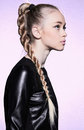 Woman with blonde hair plait in profile leather dress studio Royalty Free Stock Images