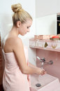 Woman the blonde in a pink towel washes hands Royalty Free Stock Images