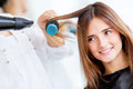 Woman blow drying her hair portrait at the beauty salon Stock Images