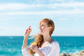 Woman blowing bubbles at the sea laughing young using a plastic ring and soap mixture Royalty Free Stock Images