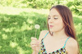 Woman blowing on dandelion Stock Photos