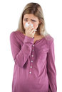 Woman blowing her nose while looking at the camera on a white background Stock Photography