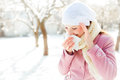 Woman blowing her nose young into a tissue in winter Royalty Free Stock Photo