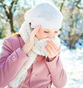 Woman blowing her nose young into a tissue in winter Royalty Free Stock Photography