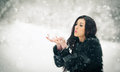 Woman blowing snow from her hands enjoying the winter. Happy brunette girl playing with snow in the winter landscape Royalty Free Stock Photo