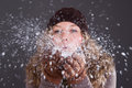 Woman blowing snowflakes young in winter clothes from her hand Royalty Free Stock Image