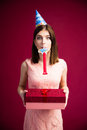 Woman blowing in whistle and holding gift box Royalty Free Stock Photo