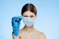 Woman on a blue background in a medical mask holds a syringe, portrait