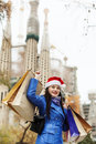 Woman in blue coat with purchases during the christmas sales smiling against sagrada familia at barcelona Royalty Free Stock Photos