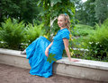 Woman in a blue dress in the arbor twined a green bindweed Stock Image