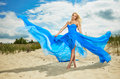 Woman in a blue dress on the beach Royalty Free Stock Photo