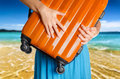Woman in blue dress holds orange suitcase in hands on the beach background Stock Photos