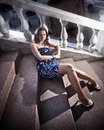 Woman in blue dress lying on stone steps outdoor beautiful sexy Royalty Free Stock Photography