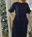 A woman in a blue dress is standing on the background of a mirror in which a Christmas tree is reflected. hands in pockets Royalty Free Stock Photo