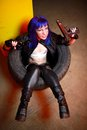 Woman with blue haircut in leather wear holding two guns sirs in the tire Royalty Free Stock Photo