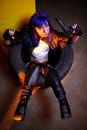 Woman with blue haircut in leather wear holding two guns sirs in the tire Royalty Free Stock Photos