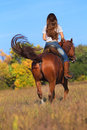 Woman in blue jeans riding a horse Royalty Free Stock Photography