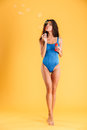 Woman in blue swim wear having fun with soap bubbles Royalty Free Stock Photo