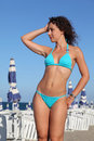 Woman in blue swimsuit stands on beach Royalty Free Stock Photo