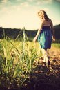 Woman in Blue Tube Dress Walking on Brown Withered Grass Under White Clouds and Blue Sky during Daytime