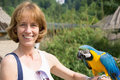 Woman with blue and yellow macaw on her arm Royalty Free Stock Photography