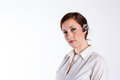 Woman with bluetooth headset a young business red hair and a serious look wears a Royalty Free Stock Photos