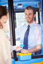 Woman boarding bus and using pass looking at driver smiling Stock Image