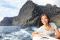 Woman on boat sailing looking at ocean smiling happy and free teno massif near los gigantes tenerife in background beautiful young Royalty Free Stock Photo