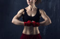 Woman body builder portrait of a young brunette with beautiful musculature on dark grunge background Stock Photography