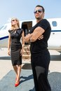 Woman with bodyguard against private jet elegant women standing Stock Image