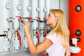 Woman in the boiler room for heating. Stock Image