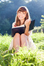 Woman with a book on green meadow laughs Stock Images
