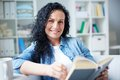 Woman with book happy brunette in casual clothes reading at home Royalty Free Stock Images