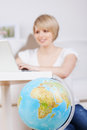 Woman booking her trip online attractive young blond with a world globe with selective focus to the globe Royalty Free Stock Photo