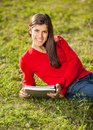 Woman with books relaxing on grass at college portrait of beautiful young campus Stock Image