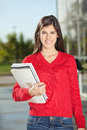 Woman with books standing on college campus portrait of confident young Royalty Free Stock Photo