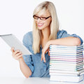 Woman with books and tablet young browsing the internet a stack of at her side Royalty Free Stock Images