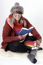 Woman with books in winterclothes holding a stack of and reading aloud Royalty Free Stock Photos