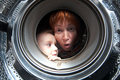Woman and boy peer into get washer Stock Image
