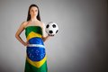 Woman in the brazilian flag and soccer ball on gray background Stock Images