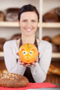 Woman with bread and piggy bank smiling holding a on the table Royalty Free Stock Image
